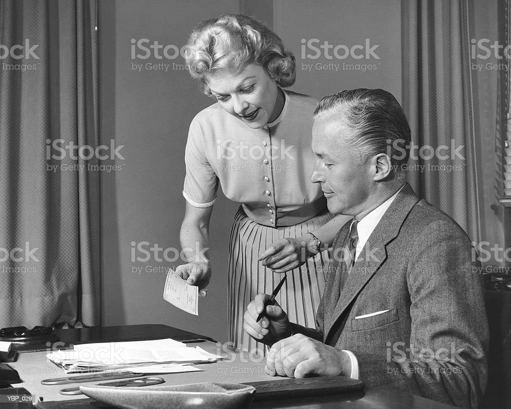 Woman showing man cheque, man holding pen royalty-free stock photo