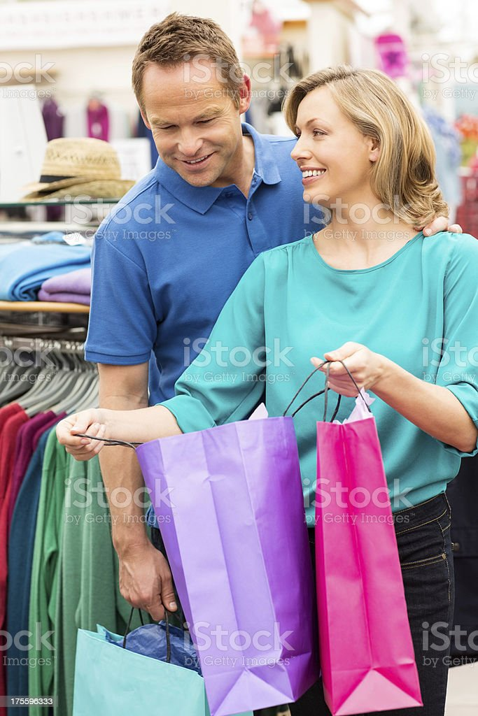 Woman Showing Man Purchases In Shopping Bag royalty-free stock photo