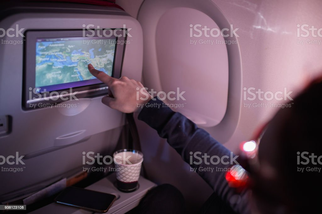 Woman Showing Map On Airplane Device Screen stock photo