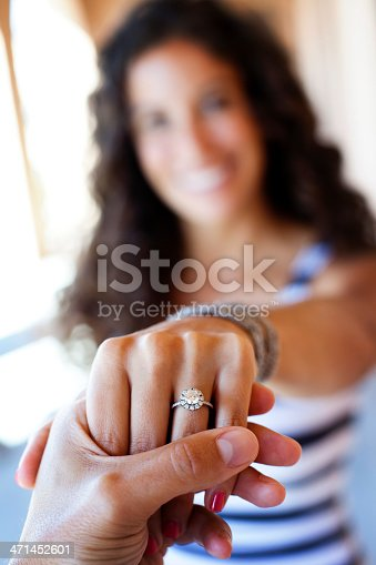 man holding fiancés hand displaying engagement ring. Shallow depth of field.