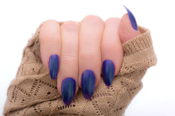 frau zeigt ihren neuen blauen nägeln und funkenbildung pullover - nails stiletto stock-fotos und bilder
