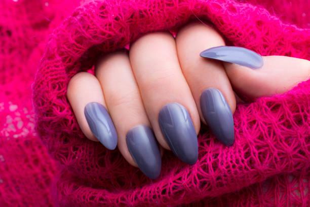 frau zeigt ihre neuen stiletto nägel und rosa strickpullover - nails stiletto stock-fotos und bilder