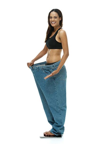 frau zeigen wie viel gewicht sie verloren hat - damen hosen größe 27 stock-fotos und bilder