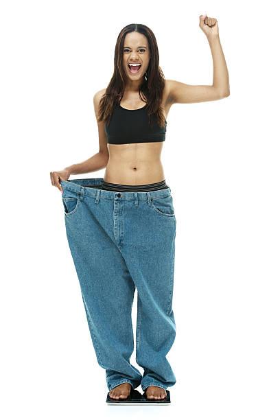 frau zeigen wie viel gewicht sie verloren - damen hosen größe 27 stock-fotos und bilder