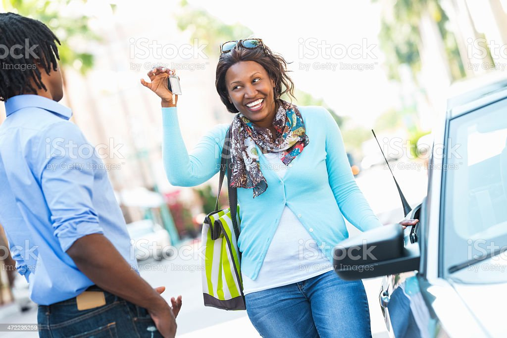 Woman showing off keys to her new car stock photo