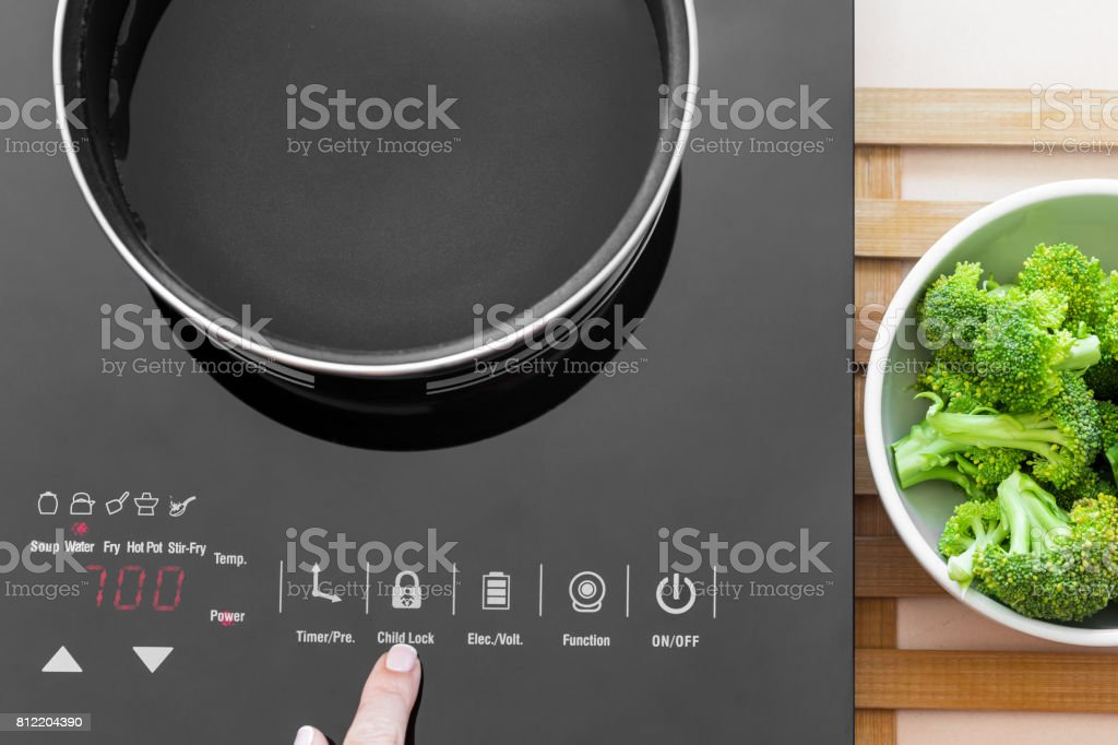 Woman showing on child Lock button on Induction stove stock photo