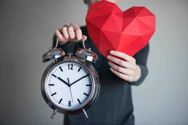 Woman showing red polygonal heart shape and alarm clock – Foto