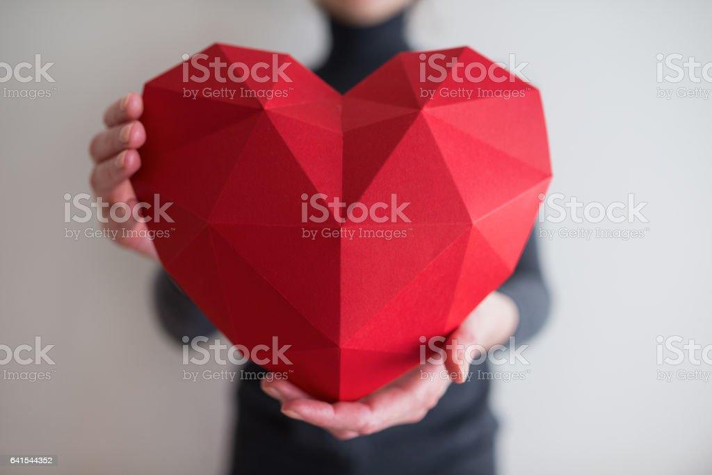 Frau zeigt rote polygonalen Papier Herzform – Foto