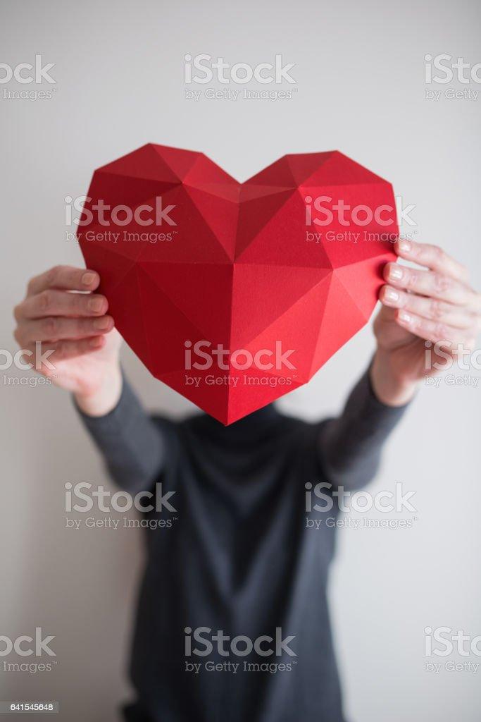 Woman showing red polygonal paper heart shape – Foto