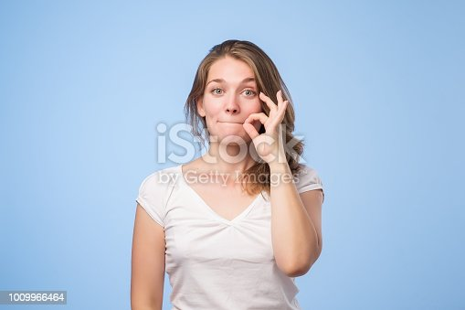 European woman showing shh sign standing on blue background
