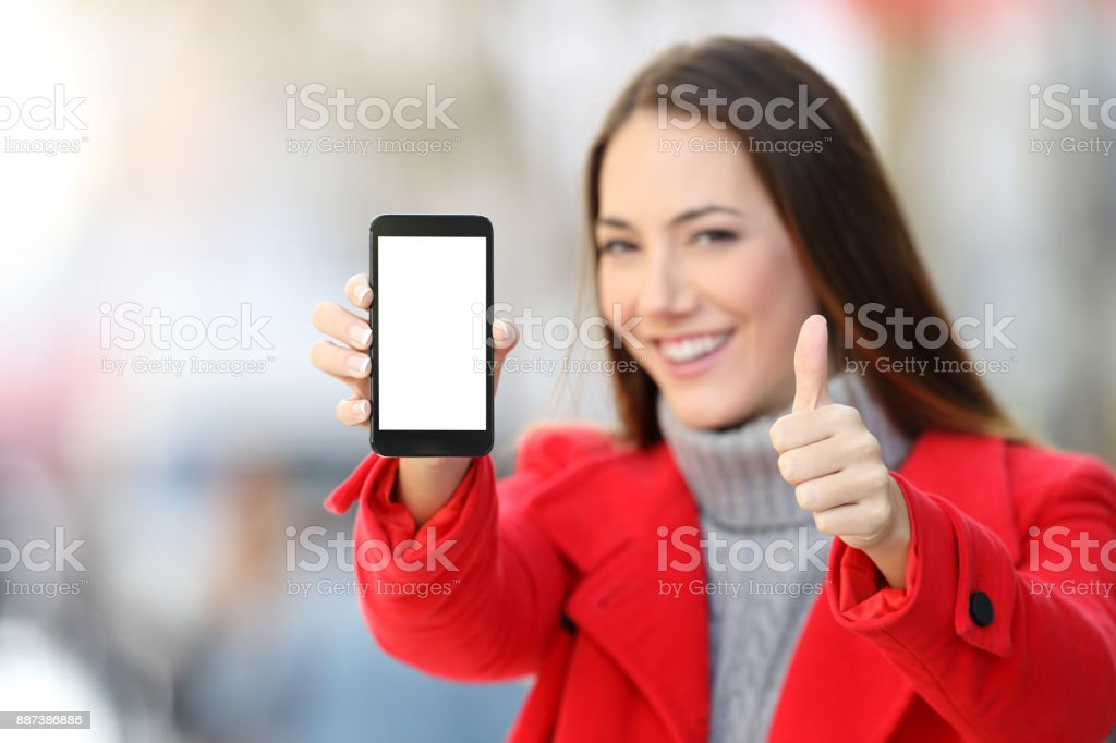 Woman showing smart phone screen in winter stock photo