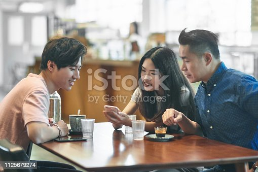 Woman showing smart phone to friends. Males and female are enjoying coffee at table. They are sitting in cafeteria.