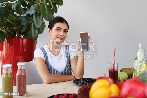 istock woman showing smartphone 898391300