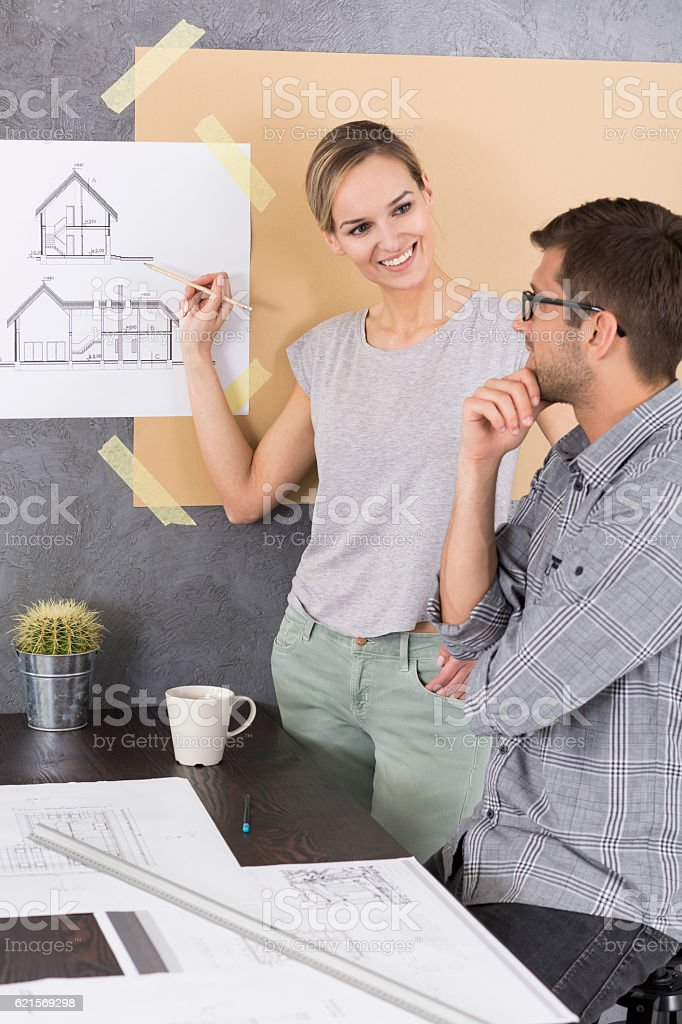 Woman showing something on a drawing to her co-worker photo libre de droits