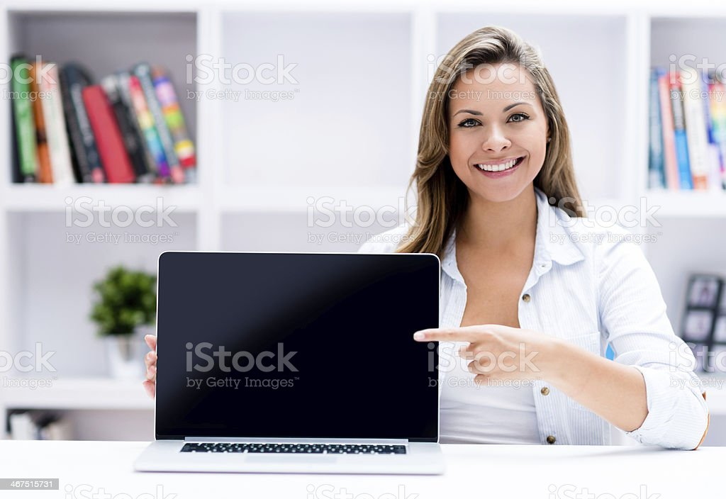 Woman showing something on a laptop Happy woman showing something on a laptop screen Adult Stock Photo