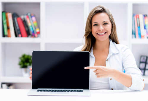 Woman Showing Something On A Laptop Stock Photo - Download Image Now