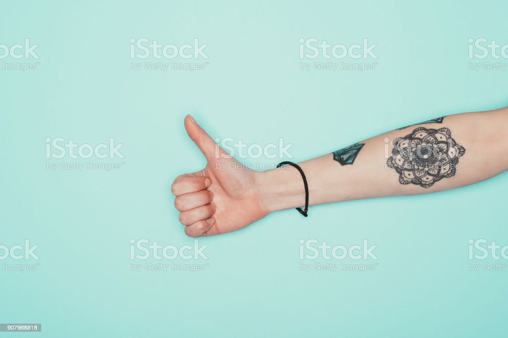 Woman showing thumb up isolated on turquoise - Stock image .