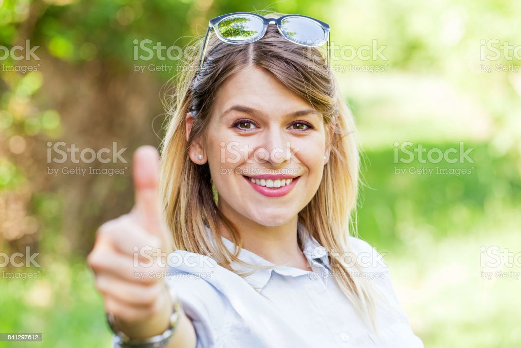 Woman showing thumbs up in the park stock photo