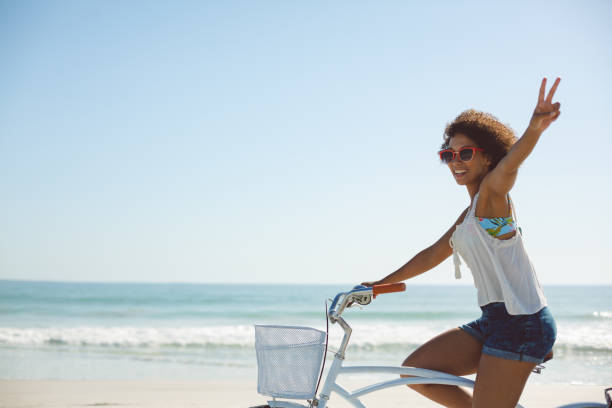 Woman showing victory sign while riding a bicycle on the beach stock photo
