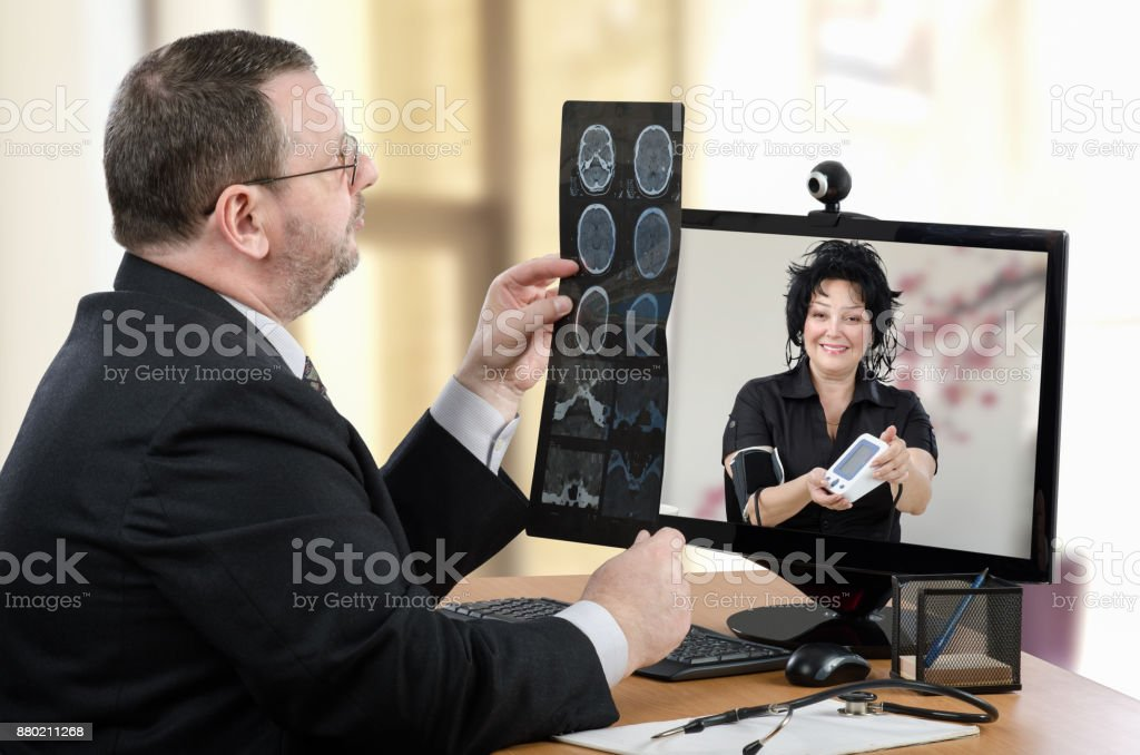 Woman shows blood pressure outcomes to virtual doctor stock photo