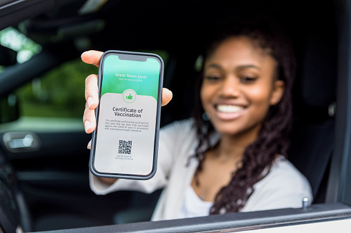 While sitting in her car, a beautiful young woman shows a digital vaccination certificate.