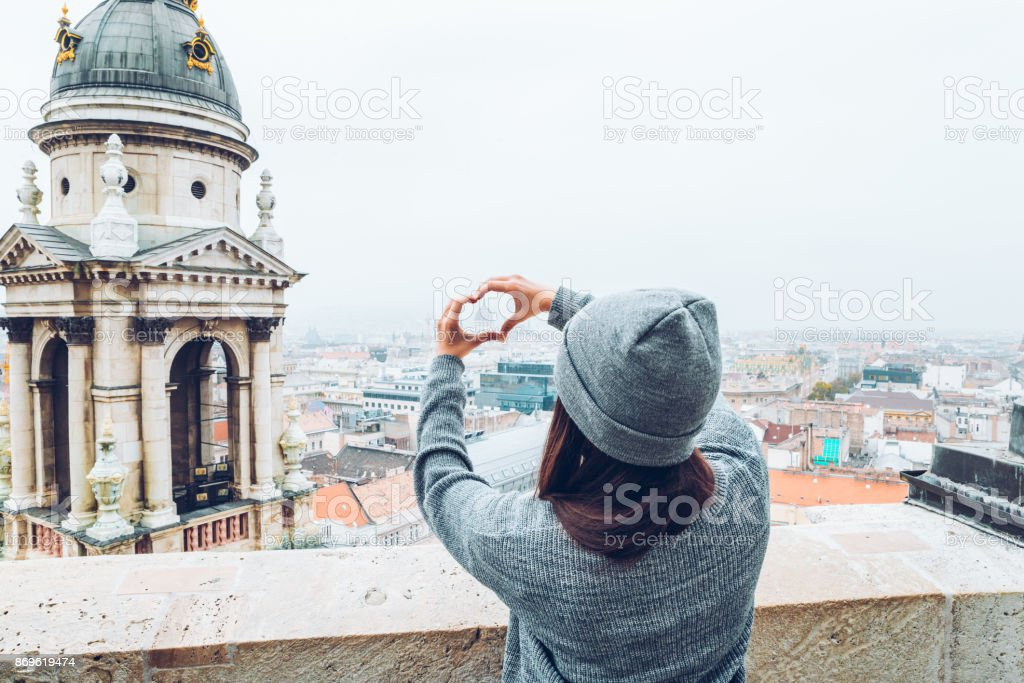 woman shows heart with hands with beautiful view of old european city on background stock photo