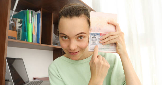 Woman shows passport with visa looking at camera Woman smiling, looking at camera and showing passport with american visa home interior green card stock pictures, royalty-free photos & images