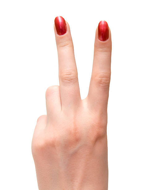 Woman shows victory sign with polished nails stock photo