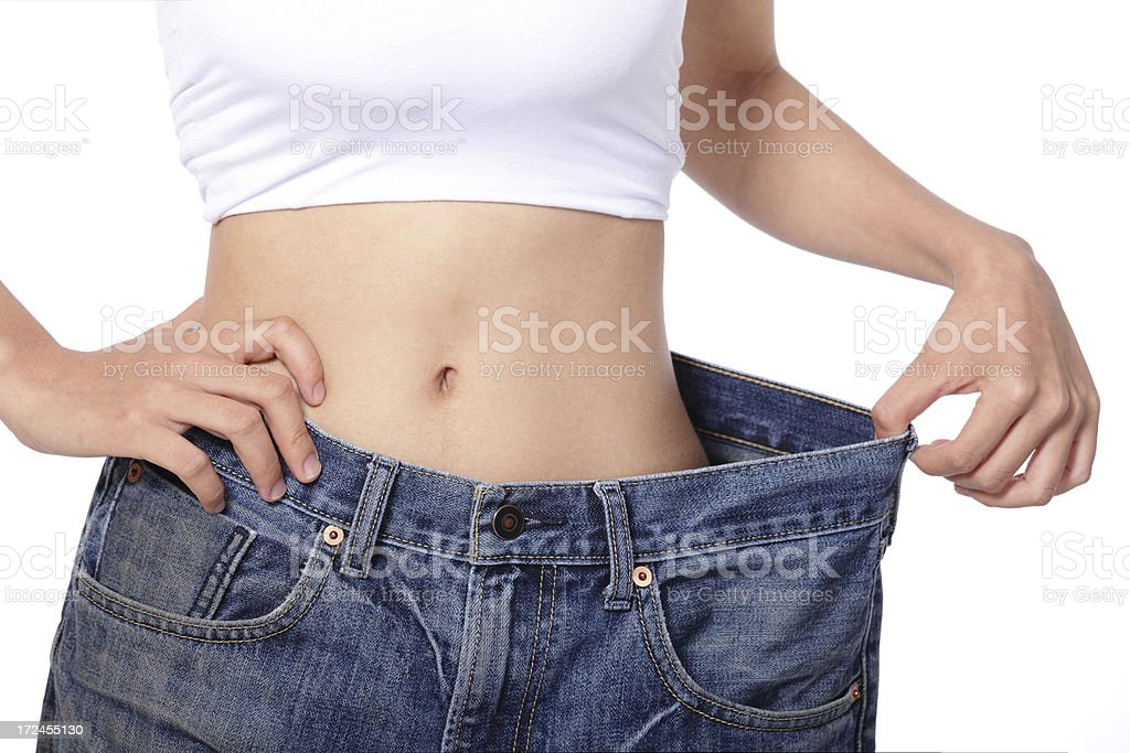 woman shows weight loss by wearing old jeans stock photo