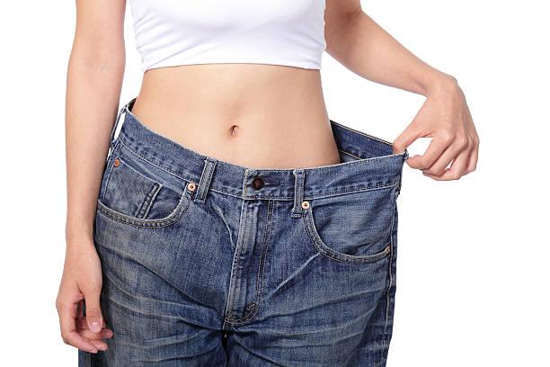 Gewicht Verlust von Frau zeigt alte jeans tragen – Foto