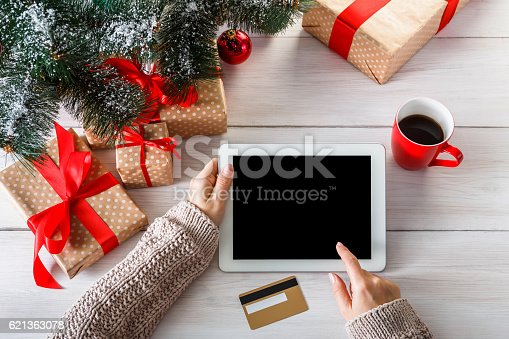istock Woman shristmas shopping online with a credit card 621363078