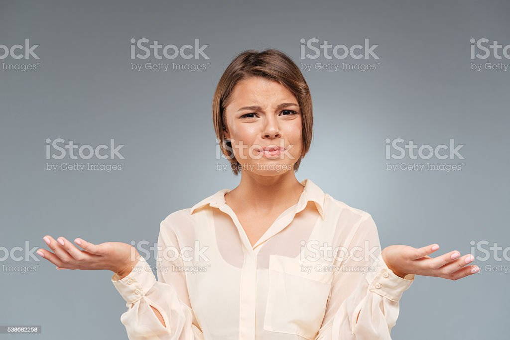 Woman shrugs shoulders with her arms out over gray background stock photo