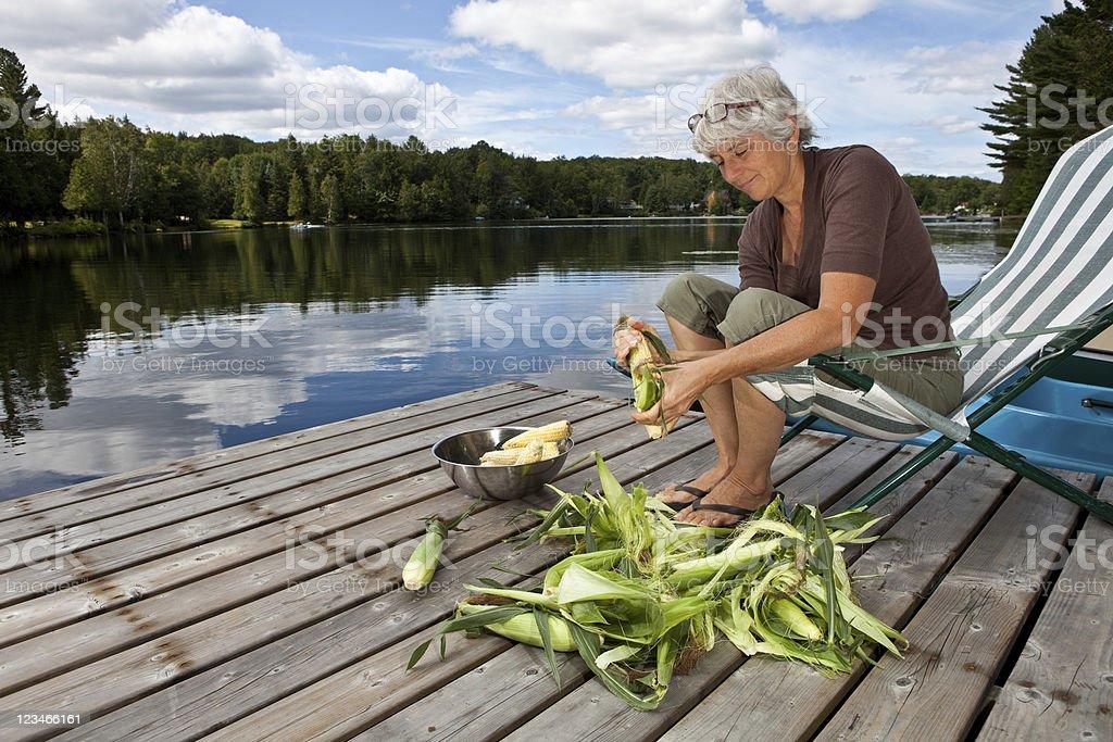 Woman shucking corn by a lake royalty-free stock photo