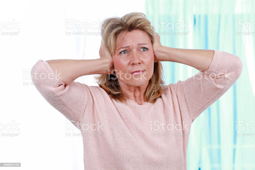 Woman shut her ears from noise stock photo
