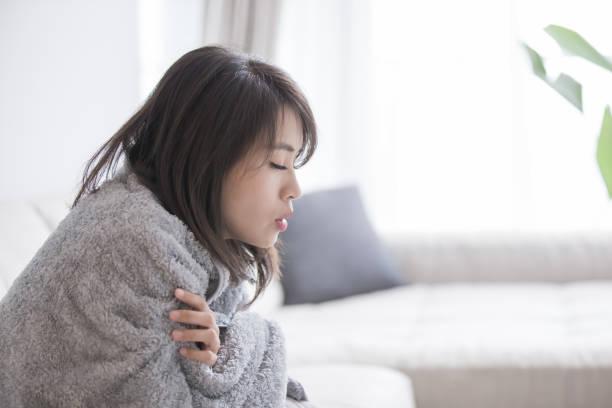 mujer enferma y siente frío - frío fotografías e imágenes de stock