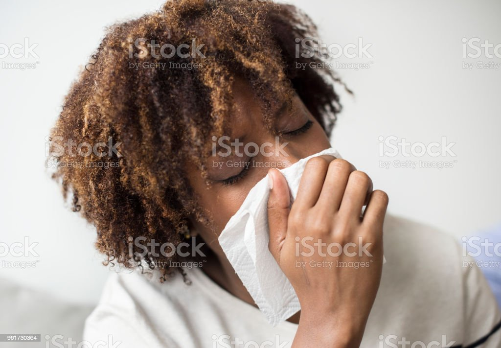 Woman sick and sneezing stock photo