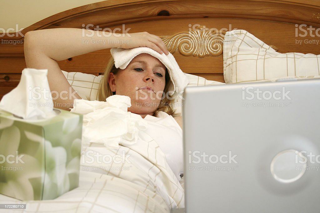 A woman sick in bed using a laptop royalty-free stock photo
