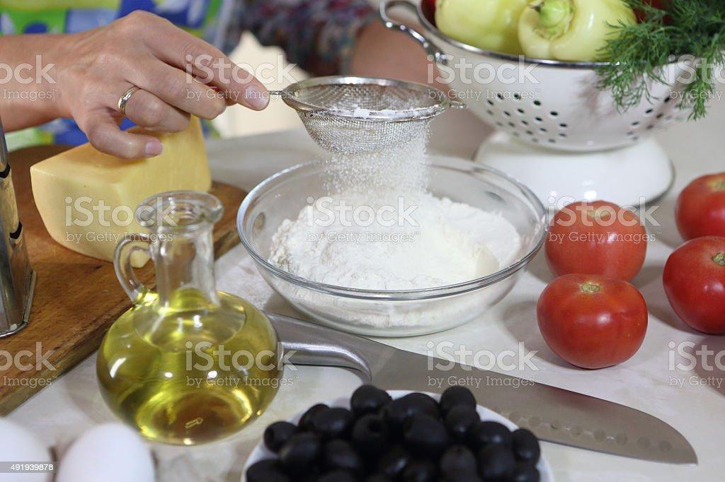 woman sifts flour stock photo