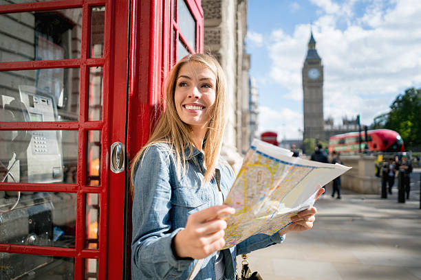 woman sightseeing in london holding a map - pauschalreise london stock-fotos und bilder