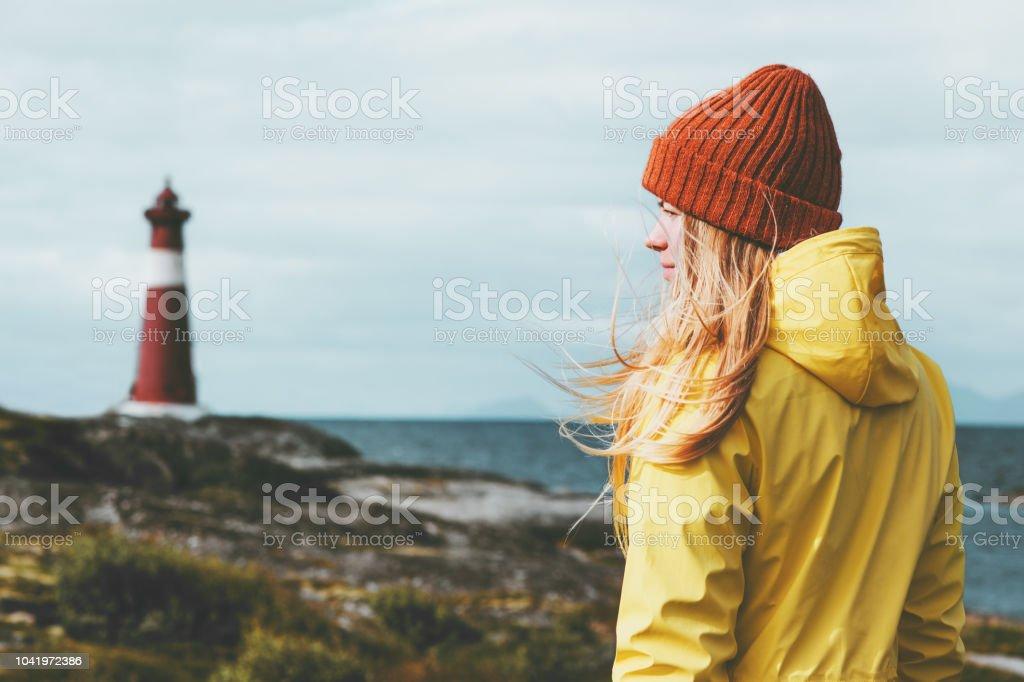 Frau Sightseeing Leuchtturm Meer Landschaft in Norwegen Reisen Lifestyle Konzept skandinavischen Urlaub im Freien. Blonde Mädchen Haare im Wind mit orangefarbenen Hut und gelben Regenmantel - Lizenzfrei Abenteuer Stock-Foto