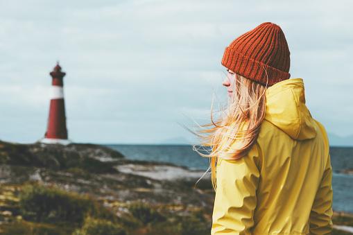 Frau Sightseeing Leuchtturm Meer Landschaft In Norwegen Reisen Lifestyle Konzept Skandinavischen Urlaub Im Freien Blonde Mädchen Haare Im Wind Mit Orangefarbenen Hut Und Gelben Regenmantel Stockfoto und mehr Bilder von Abenteuer