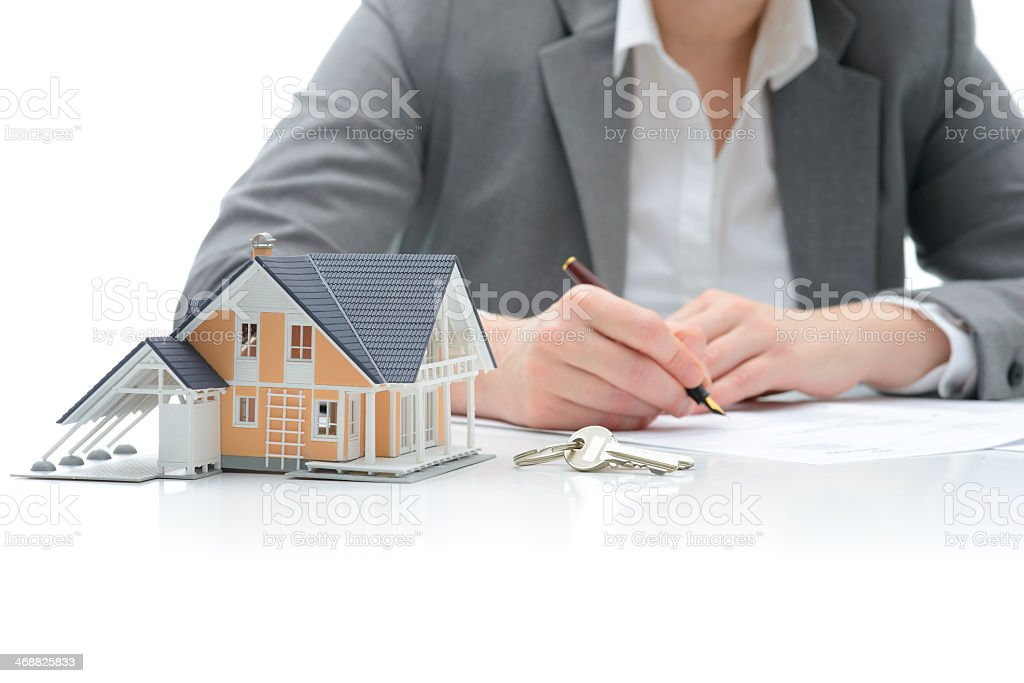 A woman signing a buyers contract for a new home stock photo