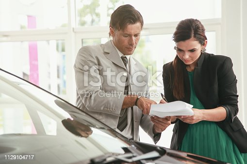 939005154 istock photo Woman signing a contract for a new car 1129104717