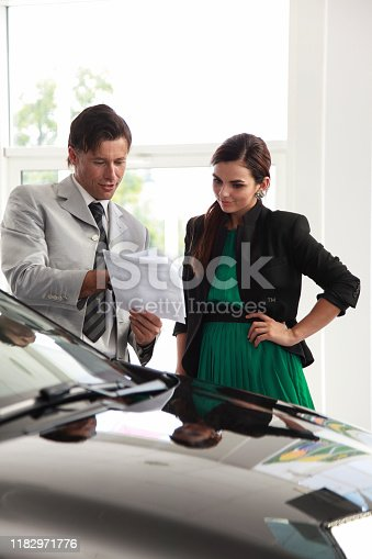 939005154 istock photo Woman signing a contract for a new car 1182971776