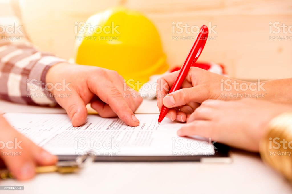 Woman signing construction contract with contractor to build a house - Foto stock royalty-free di Accordo d'intesa
