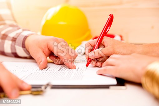 istock Woman signing construction contract with contractor to build a house 829302224