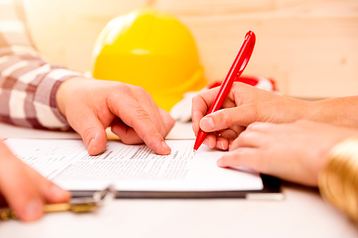 Woman Signing Construction Contract With Contractor To Build A House - Fotografie stock e altre immagini di Accordo d'intesa
