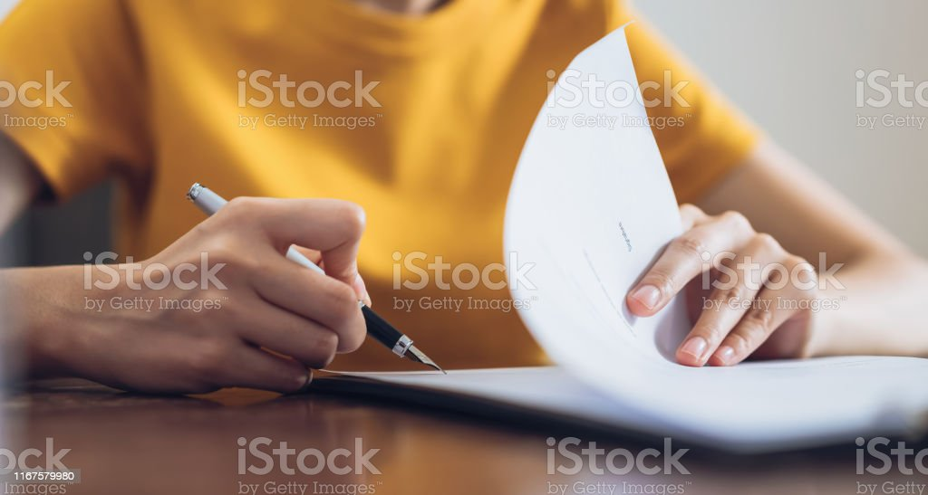 Woman signing document and hand holding pen putting signature at paper, order to authorize their rights. Woman signing document and hand holding pen putting signature at paper, order to authorize their rights. Adult Stock Photo