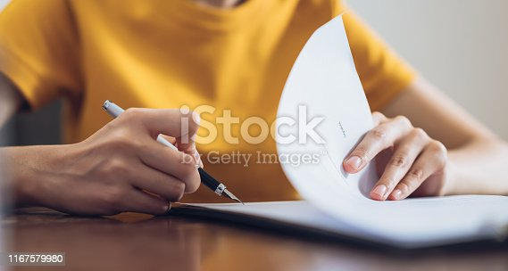 istock Woman signing document and hand holding pen putting signature at paper, order to authorize their rights. 1167579980