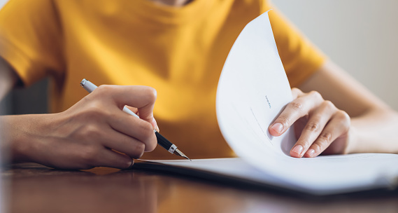 Woman Signing Document And Hand Holding Pen Putting Signature At Paper Order To Authorize Their Rights Stock Photo - Download Image Now